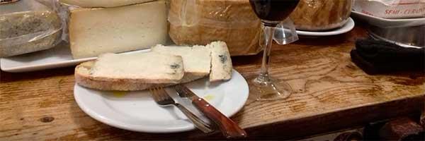 tapa de queso y vaso de vino en el almacén de vinos Casa gerardo taberna